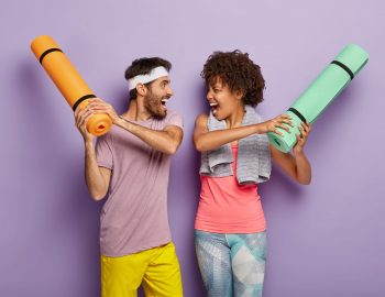 Funny multiethnic woman and man have fun in gym, fight with rolled up karemats, wear sport clothes, look at each other happily and shout loudly, have regular training together, isolated on purple wall