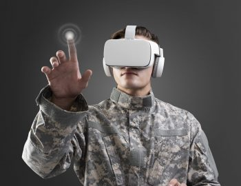 Military in VR headset touching virtual screen